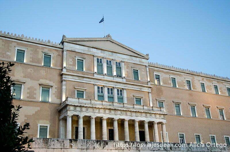 fachada del parlamento de Atenas con columnas en entrada principal y bandera en lo alto