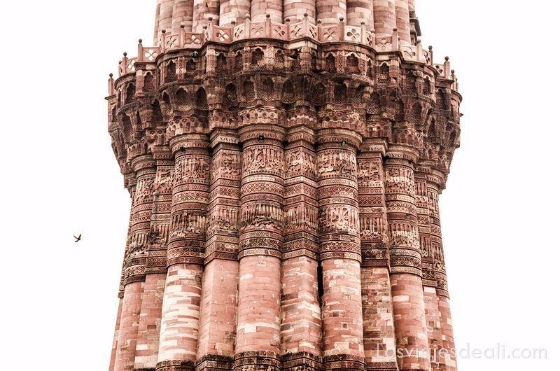 Minarete antiguo hecho con piedra rojiza y lleno de relieves con aleyas del corán qué ver en Delhi