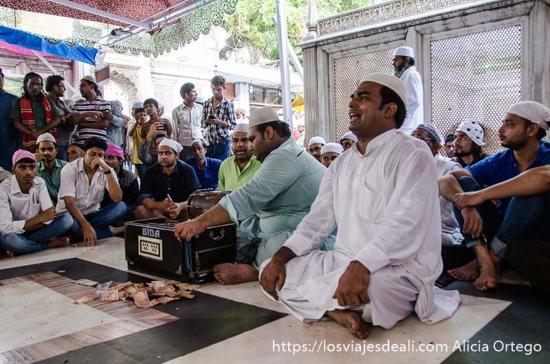 cantantes actuando sentados en el suelo y rodeados de mucha gente qué ver en delhi
