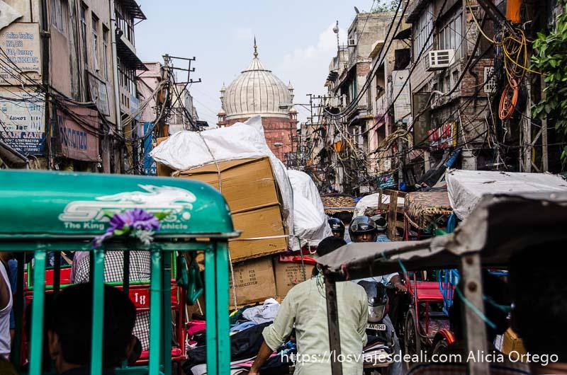 tráfico de rickshaws y mercancías donde no cabe un alfiler y cúpula de gran mezquita al fondo qué ver en delhi
