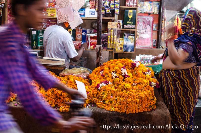 chico pasa en bici delante de puesto de flores naranjas en chadni chowk qué ver en delhi