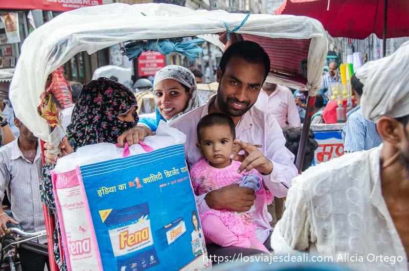 familia montada en un rickshaw el hombre con su bebé de vestido rosa en brazos y mujer  con cara tapada por velo qué ver en delhi