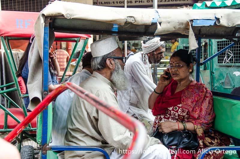 dos hombres con vestimenta musulmana y mujer con sari montados en rickshaw qué ver en delhi