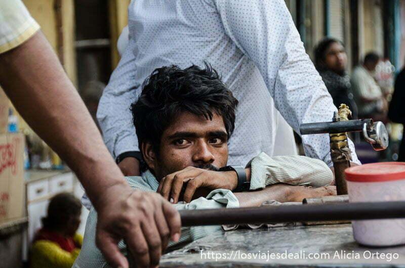 chico de mirada profunda apoyado en mostrador qué ver en delhi