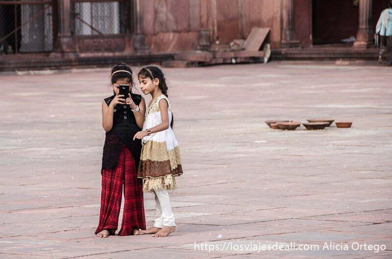 dos niñas con un móvil en el centro del patio de la mezquita qué ver en delhi