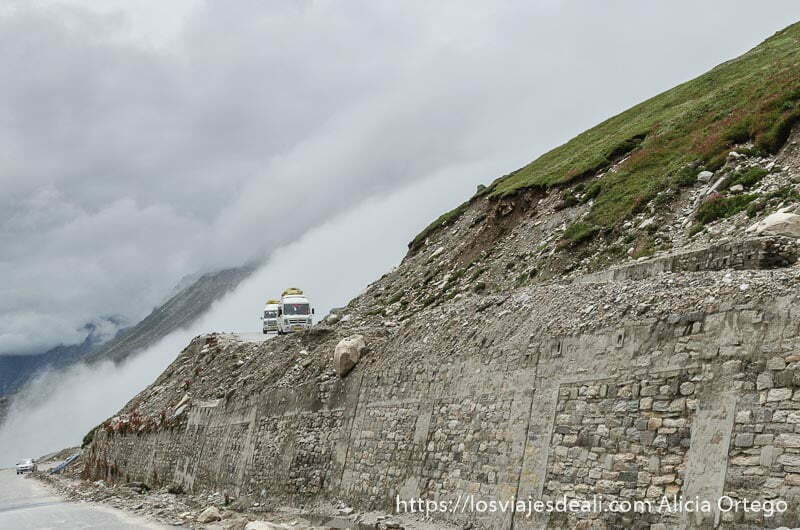 dos furgonetas avanzan por carretera detrás una gran nube carreteras del himalaya indio