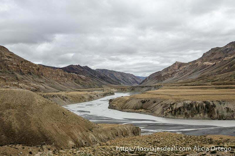 río ancho fluyendo entre montañas y cielo muy nublado carreteras del himalaya indio