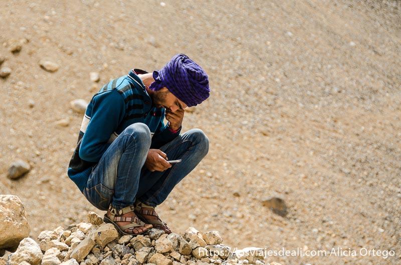 joven con turbante morado en cuclillas mirando su móvil carreteras del himalaya indio