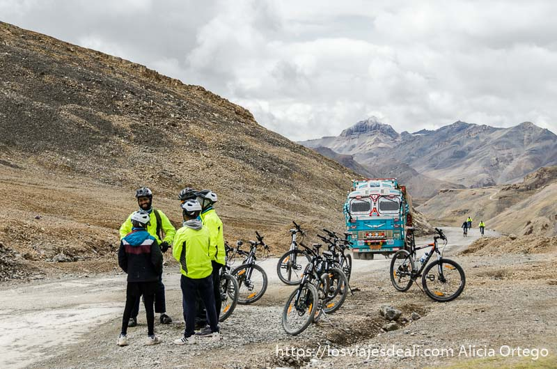 grupo de ciclistas con chaquetas amarillo fosforito en una de las carreteras del himalaya indio