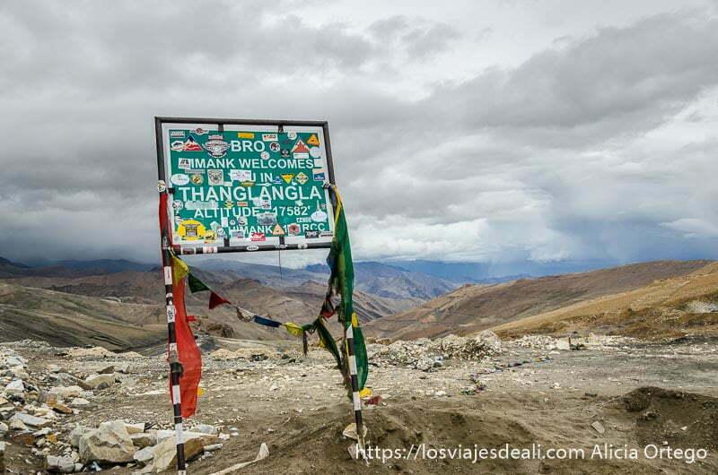 cartel con el nombre del puerto y la altitud y algunas banderas de oración detrás el paisaje de montañas con nubes