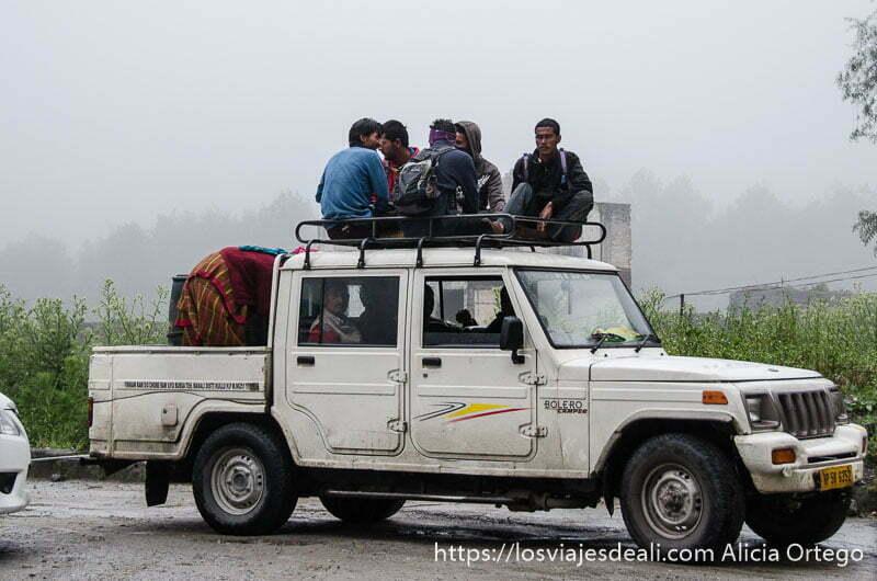 5 hombres sentados en la baca de una pick up con niebla al fondo carreteras del himalaya indio