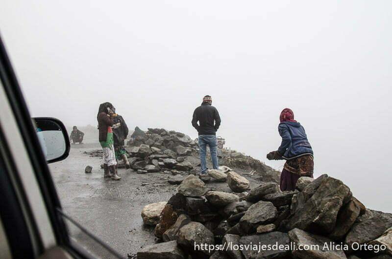 hombres y mujeres despejan la carretera a mano quitando piedras