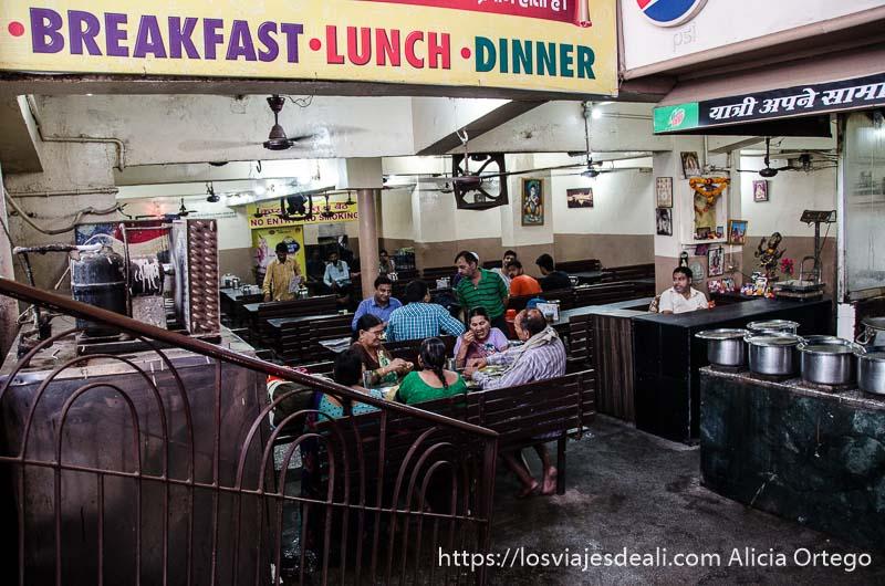 casa de comidas con la cocina vista y familias comiendo en haridwar