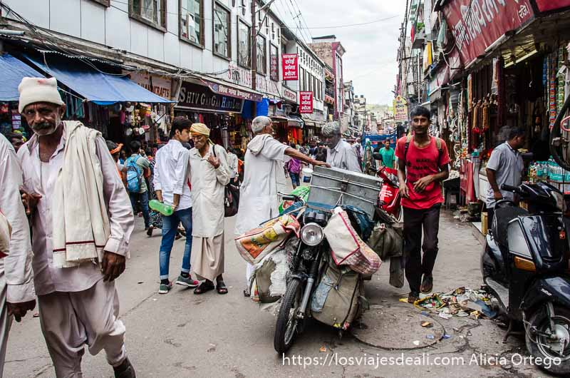 calle de haridwar llena de hombres con turbantes, motos con cajas...
