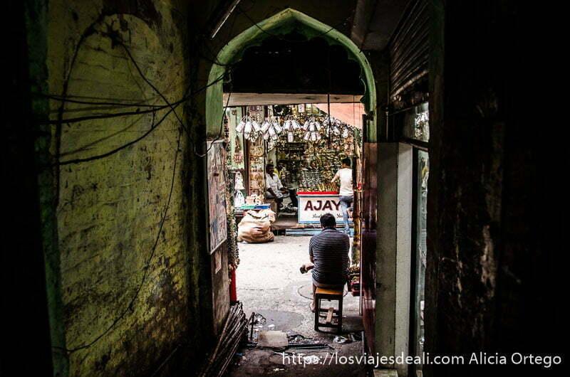 saliendo de  un edificio con portal en forma de arco y un señor sentado mirando a la calle en haridwar
