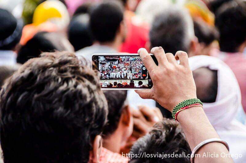 chico haciendo foto con el móvil a la multitud del festival en haridwar
