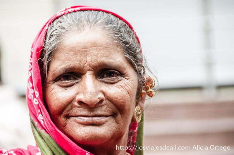 retrato de mujer mayor con sari rojo y pendientes de oro en haridwar