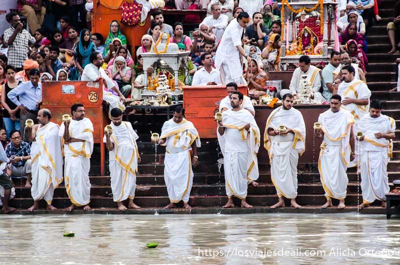 8 sacerdotes vestidos de blanco frente al agua del ganges en haridwar