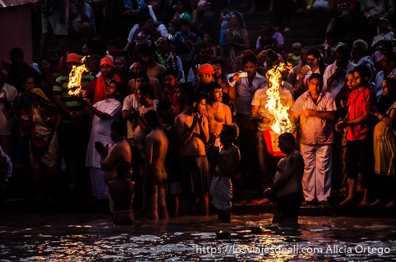 fieles a la luz del fuego entrando en el ganges en haridwar