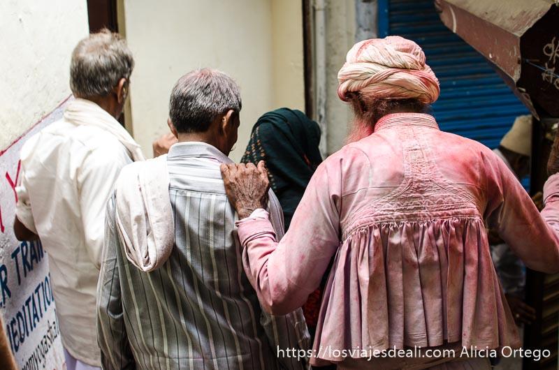 señores andando por los callejones estrechos de rishikesh uno lleva ropa blanca manchada de polvo rojo