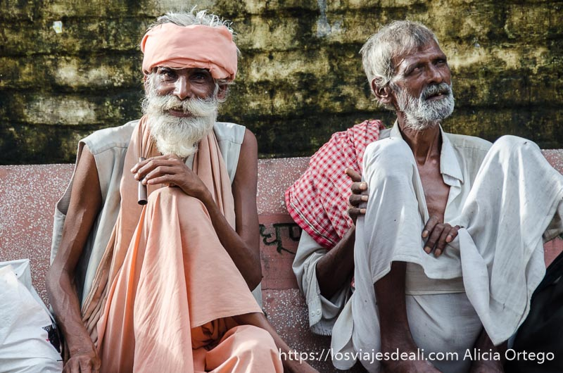 dos sadhus ancianos sentados en un banco mirando a la cámara en rishikesh
