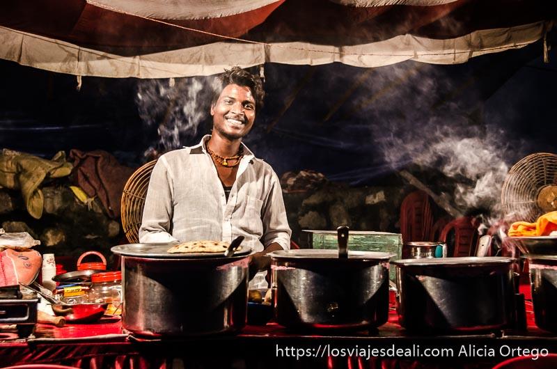 chico sonriente en su puesto de chapatis con ollas humeantes en rishiskesh