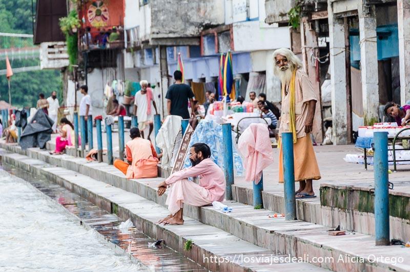 sadhus en los escalones ante el río rishikesh