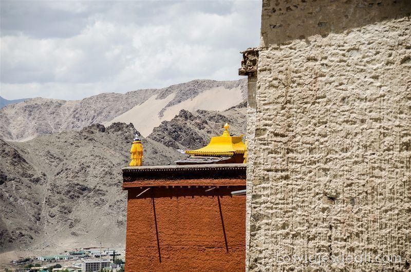 tejado de monasterio budista de color amarillo con las montañas de roca y arena detrás