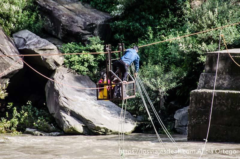 caja de metal para cruzar río con sistema de cables con dos personas montadas que ver en manali