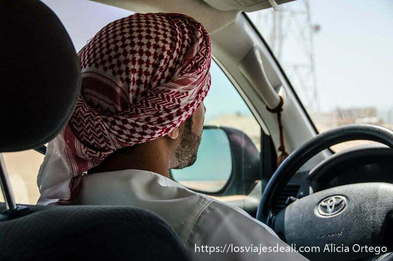 ali al volante con su pañuelo beduino de cuadros blancos y rojos desiertos de oman