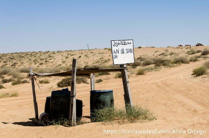 """dos bidones bajo un tejadillo y un cartel hecho a mano que dice """"oil station"""" en desiertos de omán"""