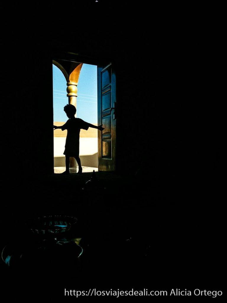 silueta de niño recortada en la puerta de su casa desiertos de oman