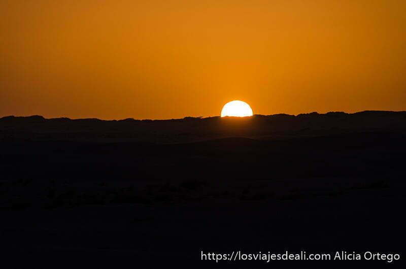 sol como gran bola poniéndose en el horizonte de dunas con cielo rojo desiertos de omán