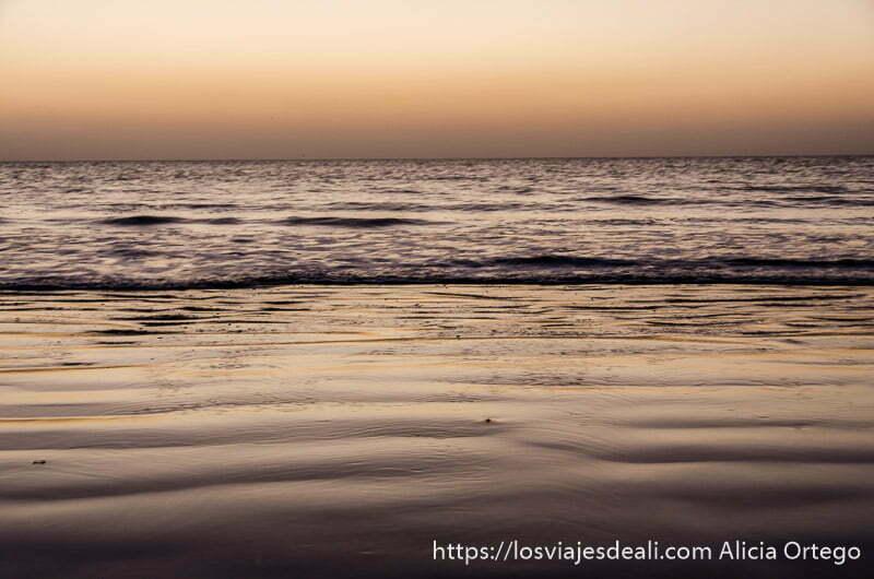 arena y agua de color naranja por el sol que está a punto de salir en playa de omán