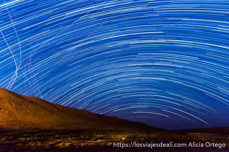 trazas de estrellas formando semicírculo sobre las dunas desiertos de oman