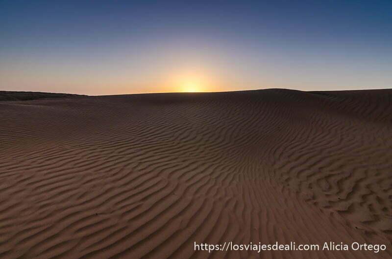 sol poniéndose sobre las dunas que tienen ondulaciones por el viento desiertos de omán
