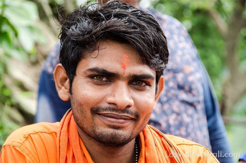 chico indio con ojos de color verde y marón y tikka naranja en la frente sonríe a la cámara.