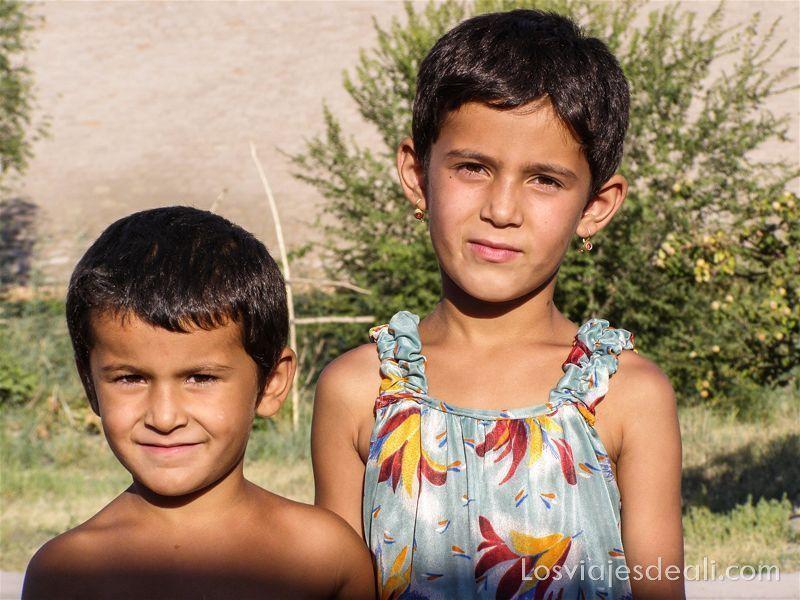 dos hermanos una niña y un niño posan ante la cámara con sonrisa y luz de atardecer
