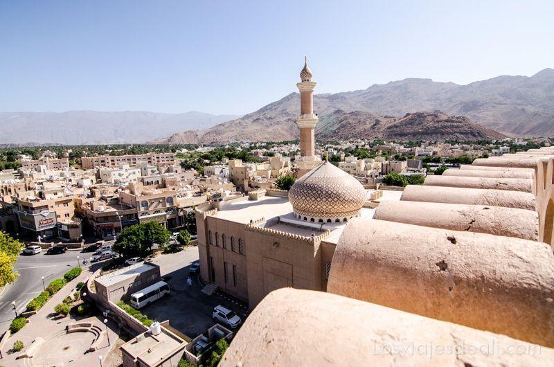 vistas de la ciudad de nizwa desde las murallas de la fortaleza y al lado la mezquita con su minarete y cúpula