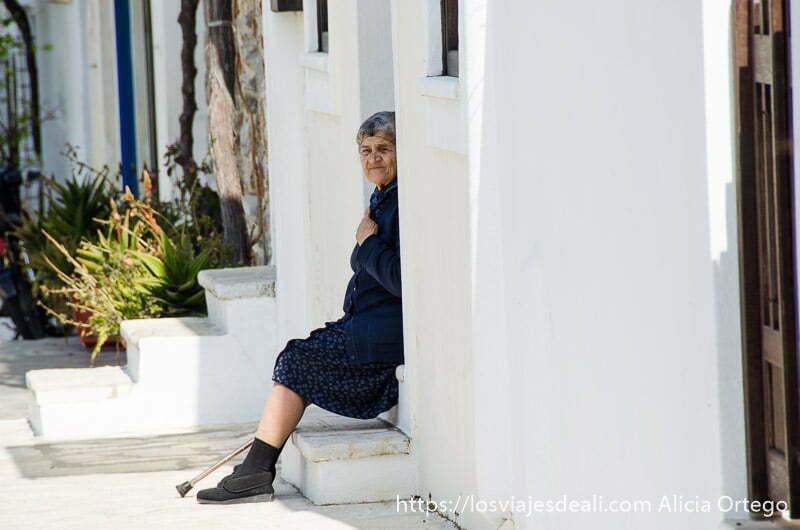 anciana con redecilla en la cabeza sentada en la puerta de su casa encalada pueblos del interior de naxos