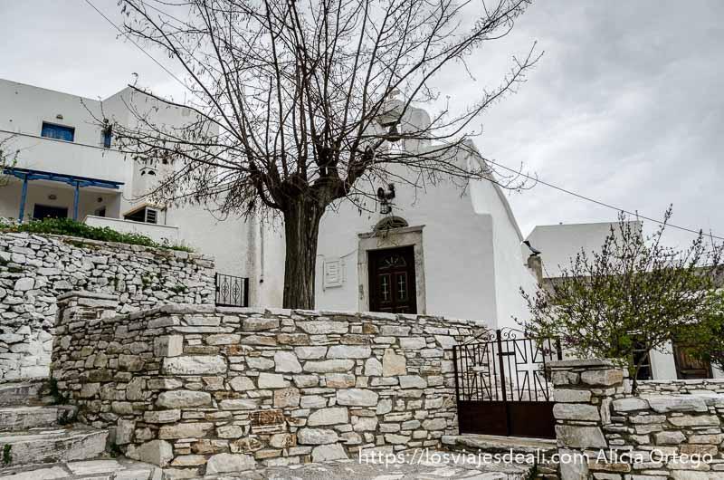 plaza de apiranthos con iglesia blanca bajo cielo nublado pueblos del interior de naxos