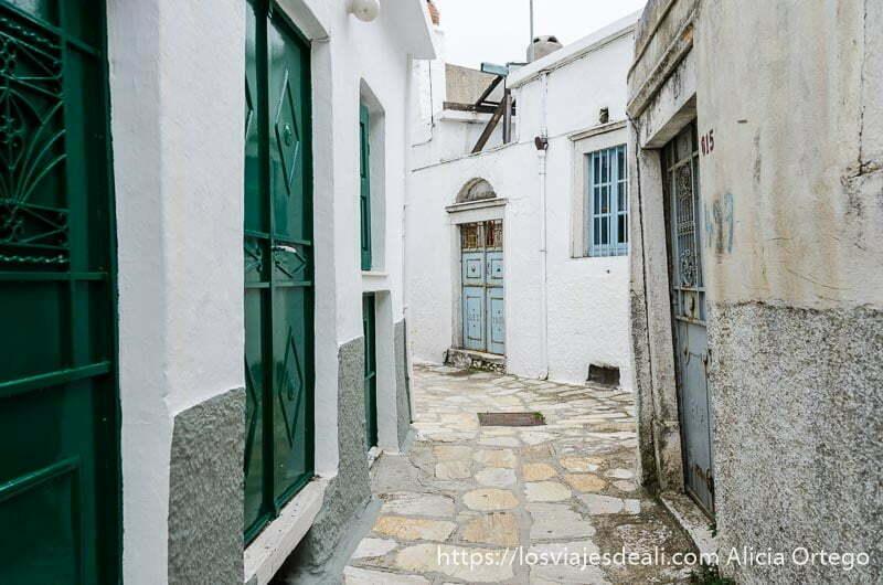calle con casas blancas y puertas de color verde y azul pueblos del interior de naxos