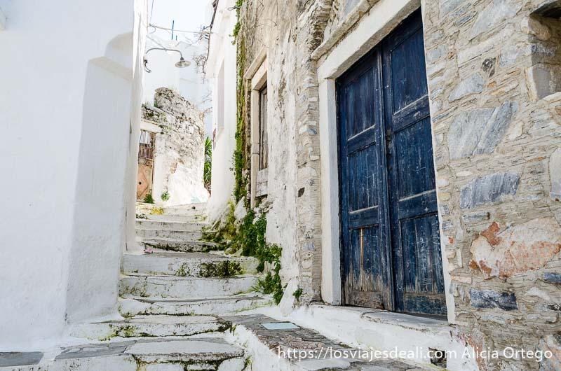 calle con escaleras todo encalado y puerta de madera azul pueblos del interior de naxos