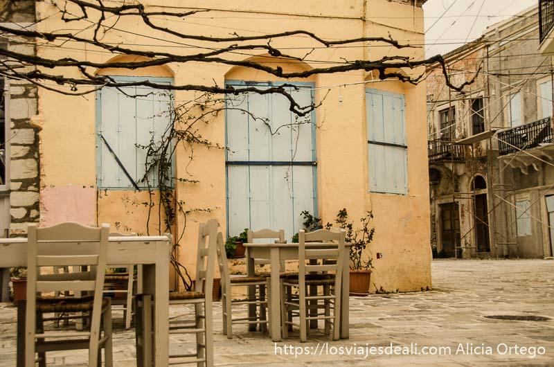 mesas y sillas de madera en una plaza vacía con taberna cerrada en halki pueblos del interior de naxos
