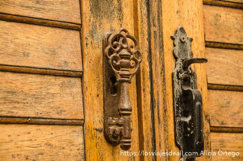 dos aldabones de hierro oxidados en una puerta de halki pueblos del interior de naxos