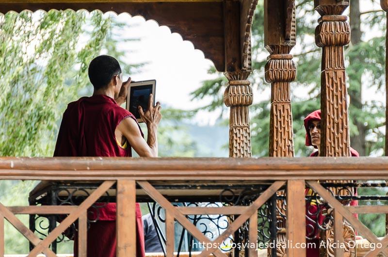 monje tibetano haciendo fotos a un compañero con su ipad