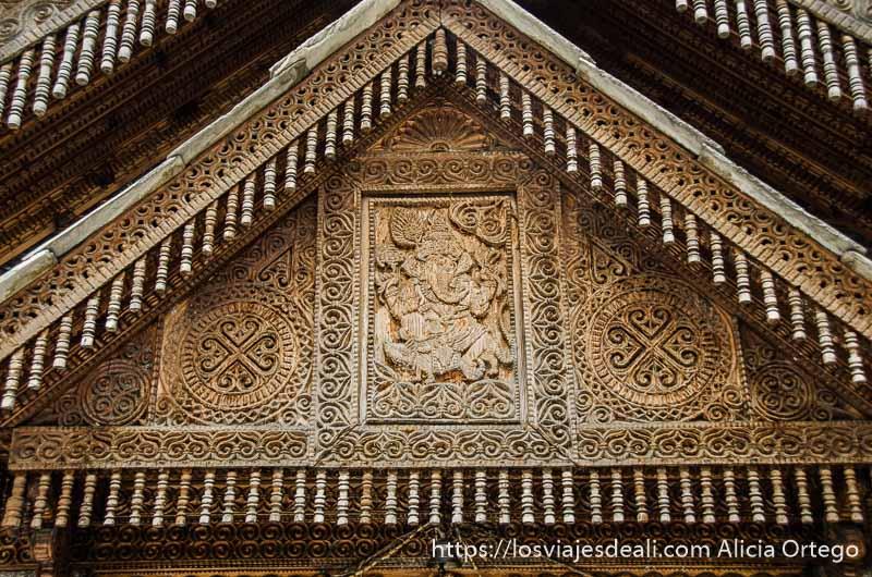 detalle de fachada del castillo toda de madera y llena de relieves con símbolos y el dios Ganesh en el centro. qué ver en Manali
