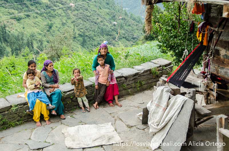 mujer con sus tres hijas y dos  niños en la terraza de su casa que da a la ladera de la montaña que ver en manali