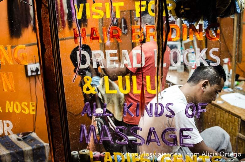 pequeño local de masajes y barbería con servicios pintados en el escaparate que ver en manali