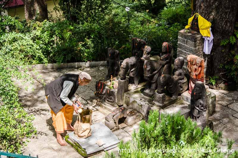 anciano preparando ofrenda ante altar de muchos dioses de piedra que ver en manali